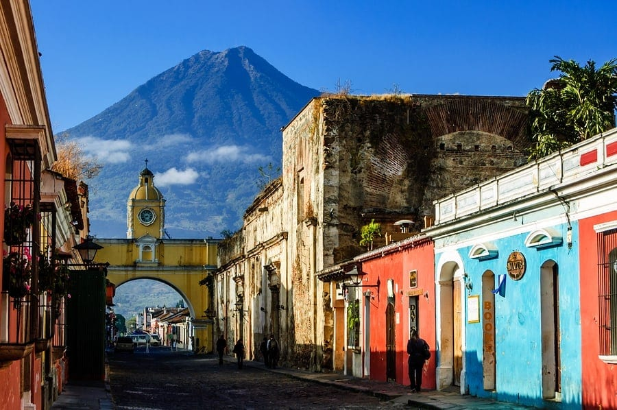 Traveling abroad can be prohibitively expensive but if you want to stretch your dollars and make the most of your vacation, check out these surprisingly affordable international spots including - Antigua, Guatemala. This photo is of locals walking to work along cobbled street with Agua volcano behind Santa Catalina Arch in Spanish colonial town & UNESCO World Heritage Site.